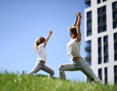 Mother and daughter together practicing yoga outside on a grass together urban city on blue sky background Фото со стока
