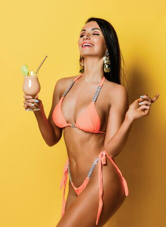 Joyful tanned slim brunette woman in sexy pink beach bikini drinks takes pleasure drinking stylish powder pink fresh cocktail. Hot summer beach swimsuits and looks for women