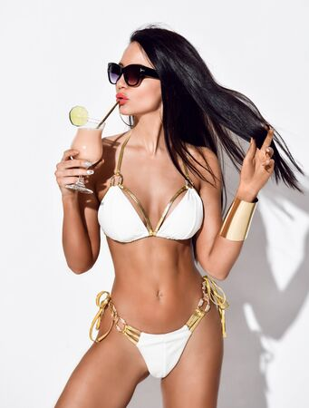 Brunette woman with perfect tanned body in sexy white beach bikini with golden trims drinks stylish powder pink cocktail. Hot summer beach swimsuits and looks for women Фото со стока
