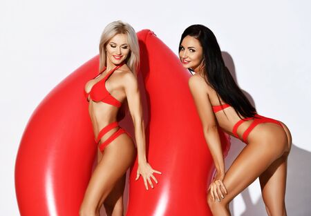 Summer vibes. Two excited young slim women blonde and brunette with perfect bodies in sexy red bikini have fun posing with big inflatable red lips going to ride float