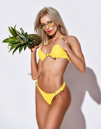 Young beautiful tanned slim blonde woman in sexy yellow bikini and smoked glasses holds carries fresh pineapple. Hot summer beach swimsuits and looks for women
