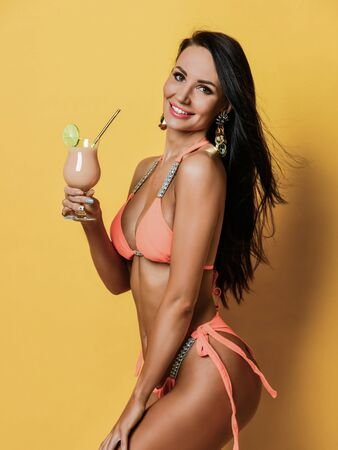Brunette woman with perfect tanned body holds  pink cocktail and smiling.