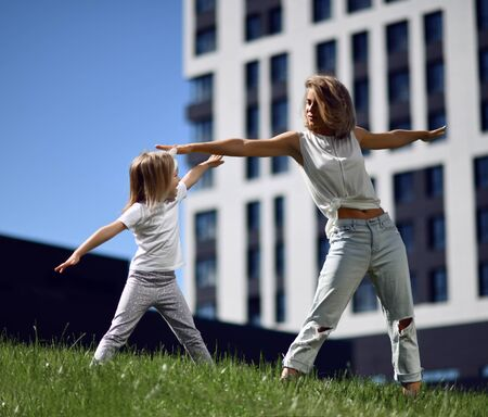 Mother and daughter working out practicing yoga outside on a grass together urban city  park on blue sky background