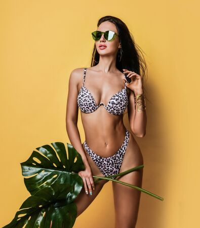 Young tanned slim brunette woman in sexy leopard bikini and sunglasses is standing holding tropical leaves on yellow background. Hot summer beach swimsuits and looks for women