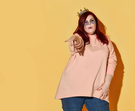 Flirting red haired plus size woman in casual clothing and golden crown on head points finger at us over yellow background with copy space. Stylish look of pretty overweight woman