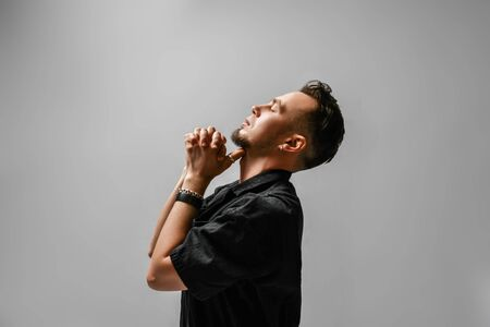 Side view of young brutal man in black casual clothing and earrings holding head up with eyes closed hands at beard fingers interlocked. Men style and face expressions concept