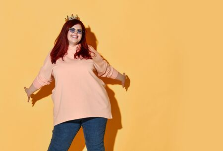 Joyful red haired plus size woman in casual clothing and golden crown on head stands with her arms spread wide over yellow with copy space. Stylish look of pretty overweight woman