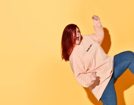 Happy plus size woman in jeans and hoodie gestures win luck yes sign, holding fist and knee up over yellow background with copy space. Stylish look of pretty overweight woman Stock Photo