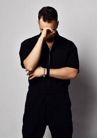 Portrait of tired young brutal man in black denim overall stands looking down with hand at his elbow over grey background. Fashion for men and face expressions concept