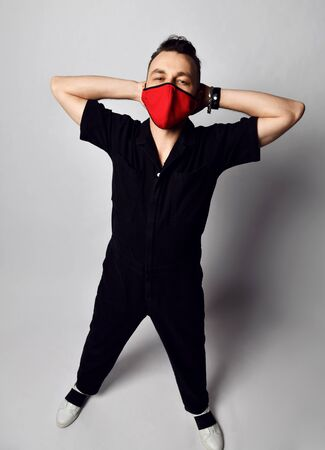 Young man in black overall and red medical mask for protection from coronavirus infection stands holding hands on head over grey background. Stylish virus protection concept