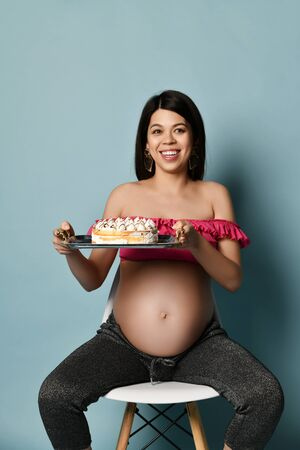 Happy smiling young pregnant brunette woman in pink top and sits on chair holding cake with cream on tray over blue
