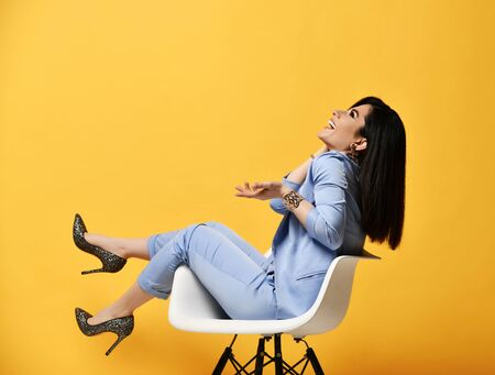 Laughing woman stylish brunette in blue official suit and high-heeled shoes sitting in designer armchair posing like she is holding something on her open palm on yellow background