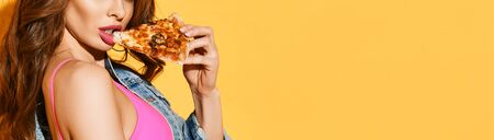 Close-up of young curly brunette woman with pouty lips wearing pink bra and denim jacket eating pizza over yellow background. Sexy fit womans body and fast food concept. Banner
