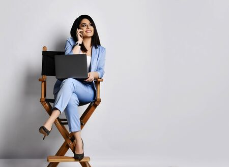 Business woman in official suit sitting with laptop on armchair is glad to hear her business partner by cell phone on white background with free text copy space Фото со стока