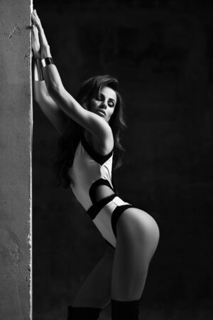 Excited sensual brunette woman in sexy white bodysuit with trims is leaning against concrete wall and looking at perfect buttocks over dark background. Sexy womans body concept