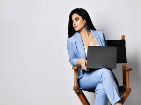 Strict business woman in blue official pantsuit formal wear sits with black laptop on wooden armchair and looks sternly at something on the side of her