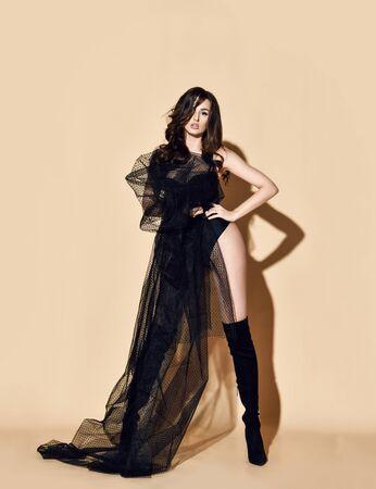 Große, edle brünette Frau posiert in einem schwarzen Kleid aus transparentem Stoff und Body und in hohen Stiefeln. Sexuelles feminines Look-Konzept