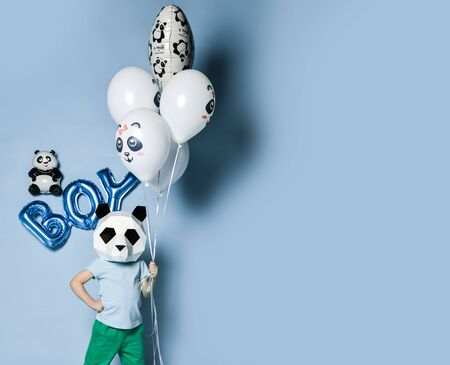 Happy little boy kid in panda mask with bunch of balloons for birthday party with free text space on pastel blue background. Translation  from Russian on balloon: I love you Imagens