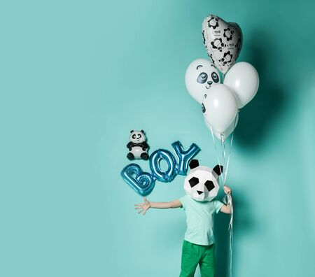 Cute kid boy in panda mask t-shirt and pants is holding balloons for birthday party on pastel blue background with free copy space. Translation from Russian on balloon: I love you