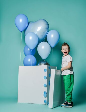 Happy screaming laughing kid boy in white t-shirt and green pants is surprised by at pastel color blue balloons for birthday party flying out of big white box he has just opened Фото со стока