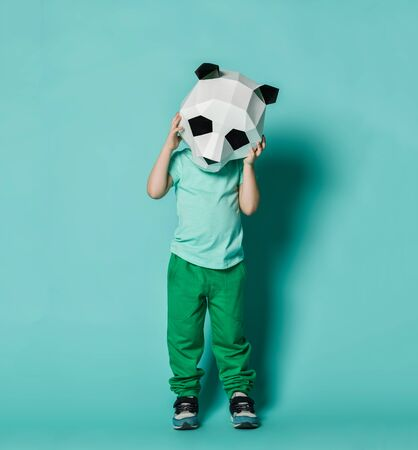 Sad kid boy in panda mask white blank t-shirt and green pants is holding his head with hands as if he is disappointed feels headache bad grief on pastel blue background
