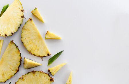 菠萝水多的黄色切片背景。顶视图新鲜的菠萝切片零件在白色