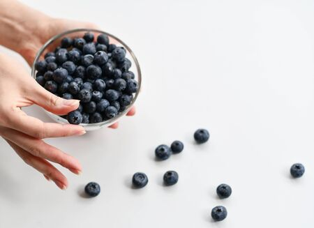 Woman demonstrates holds with two fingers a blueberry and holds a full bowl of it in the other hand over background with copy space. Organic superfood concept for healthy eating