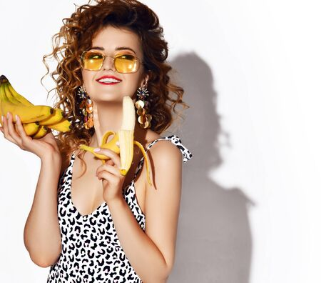 Young smiling curly woman in leopard pattern bikini standing and holding heap of fresh banana fruits in hands over white wall background. Beauty of womans body and healthy lifestyle concept