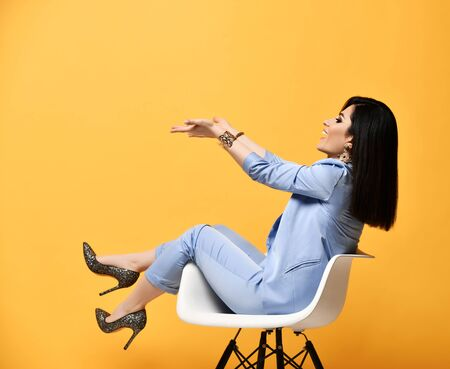 Laughing woman stylish brunette in blue official suit and high-heeled shoes sitting in designer armchair holding something on her open palms at arms length on yellow background Stock Photo