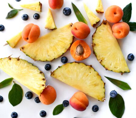 Whole and halved juicy apricots, fresh blueberries, slices of pineapple are over white background. Organic superfood concept for healthy eating