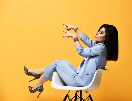 Young woman brunette in blue official suit and high-heeled shoes sitting sideways in designer armchair pointing her fingers at something on yellow background Фото со стока