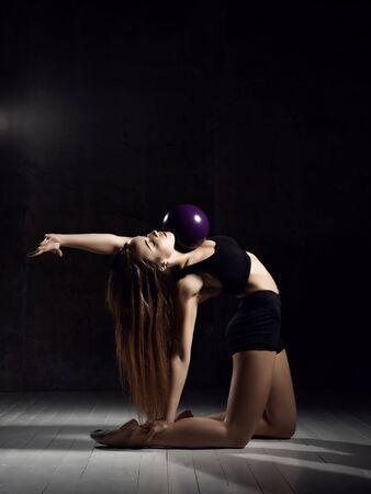 Young sporty woman doing gymnastics stretching fitness exercises workout with purple ball in gym sport club on dark background