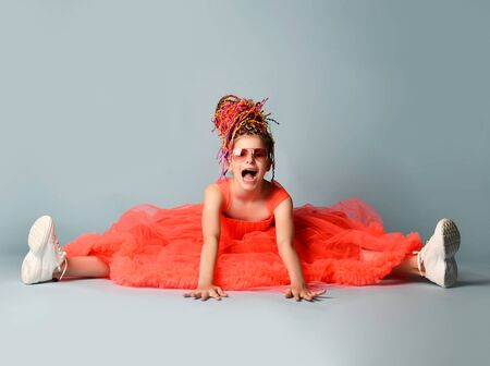 Smiling girl with colorful dreadlocks hairstyle in bright coral dress with fluffy hem, sneakers and suglasses sitting on floor with legs stretched out and shouting over grey background