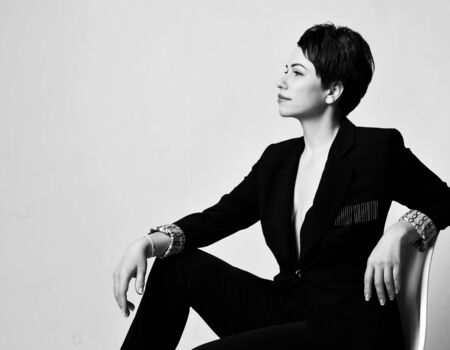 Young beautiful short haired brunette woman in elegant business suit with deep neckline sitting on chair and looking aside over white background. Business elegance concept