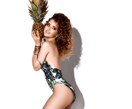 Flirty smiling curly woman in floral swimsuit stands side to us holding fresh pineapple at her cheek and looks back over white background. Beauty of womans body and healthy lifestyle concept