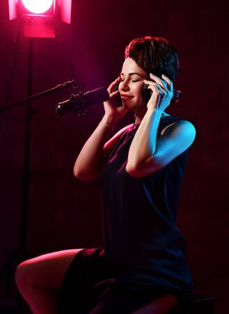 Young smiling beautiful short haired brunette woman singer in black dress sitting in studio in headphones and listening to music with eyes closed over dark background. Stylish singer concept