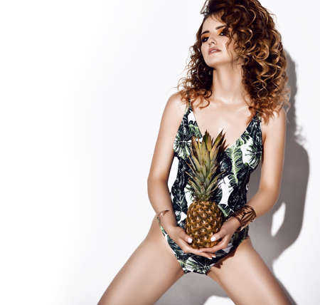 Sexual curly woman in floral pattern swimsuit stands with her legs wide apart holding fresh pineapple in hands over white background with copy space. Beauty of womans body and healthy lifestyle