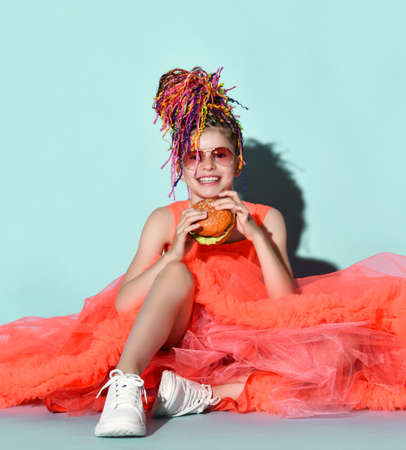 Smiling girl with colorful dreadlocks hairstyle in bright coral big dress with fluffy hem, sneakers and sunglasses sitting on floor and eating cheeseburger over grey background. Fast food concept
