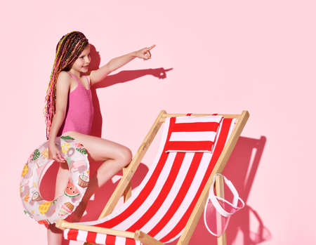 Smiling teen girl with colorful dreadlocks in pink swimsuit standing at deckchair with swimming ring and pointing at corner over pink background, copy space. Summer vibes and vacation concept 写真素材