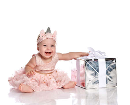 Seven month Infant child baby girl toddler sitting smiling laughing celebrating birthday with silver present gift box in stylish pink dress isolated on a white background