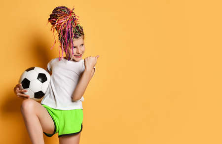 Lucky girl with colorful dreadlocks hairstyle in t-shirt and shorts holds soccer ball in hand gesturing Win Yes Goal sign over yellow background with free copy space. Pretty girls in football concept Reklamní fotografie