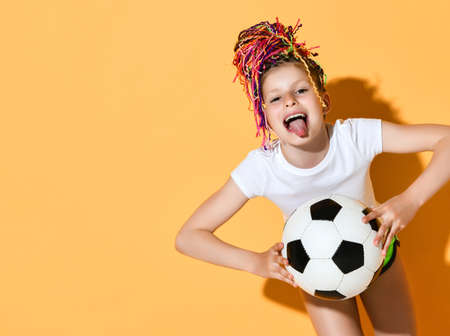 Frolic girl with colorful dreadlocks hairstyle in t-shirt and shorts holds soccer ball with both hands stick out her tongue teasing over yellow background with free copy space. Pretty girls in football concept Reklamní fotografie