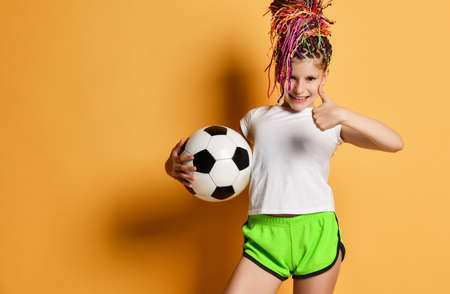 Lucky girl with colorful dreadlocks hairstyle in t-shirt and shorts holds soccer ball in hand gesturing thumb up like sign over yellow background with free copy space. Pretty girls in football concept