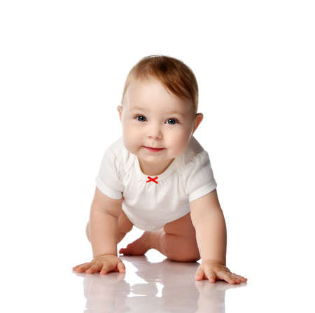 Adorable smiling curious little baby infant in white cotton bodysuit crawling creeping forward at camera over white background. Happy childhood concept