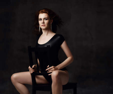 Portrait of elegant sensual tall red-haired woman in black bodysuit underwear and earrings sitting on chair backwards looking at camera over dark background. Sensual stylish images of woman concept
