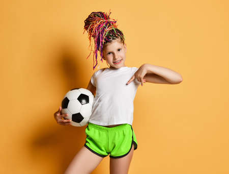 Smiling girl with colorful dreadlocks hairstyle in t-shirt and shorts stands with soccer ball in hand pointing at copy space on her white t-shirt over yellow background. Pretty girls in football concept