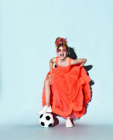 Mocking girl with colorful dreadlocks in bright coral big dress, sneakers and sunglasses stands with soccer ball under foot laughing loud. Girls in football concept