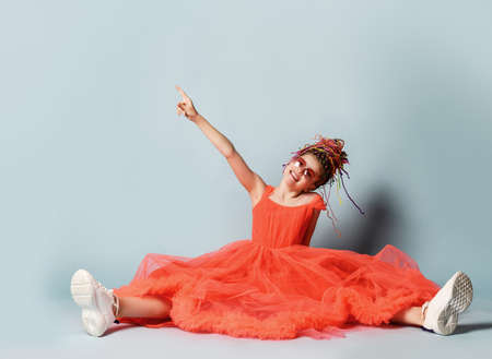 Frolic girl with colorful dreadlocks hairstyle in coral big dress with fluffy hem, sneakers and sunglasses is sits on floor with legs stretched pointing finger at copy space upper corner