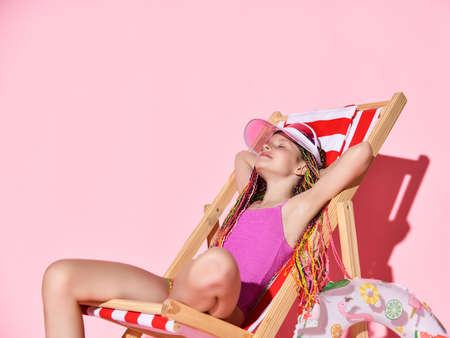 Joyful smiling girl with colorful dreadlocks in pink swimsuit takes rest sitting in deckchair lounge chair with closed eyes over pink wall background, copy space. Summer vibes and vacation concept 版權商用圖片