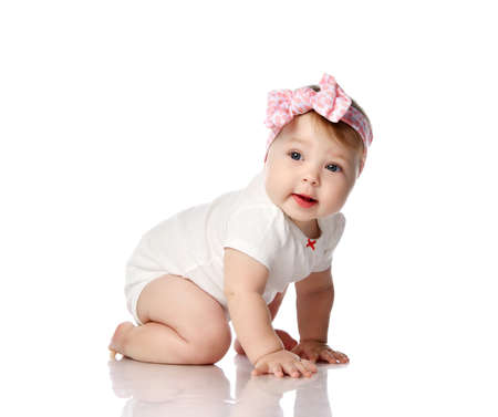 Interested and curious little baby girl in white bodysuit and with hair bow decoration crawls on floor side to us looking at camera over white background. Happy childhood concept Foto de archivo